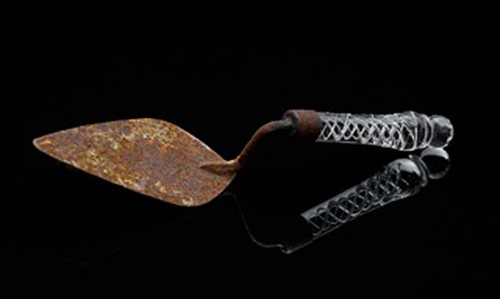 Sculpture on dark reflective background, of a rusty trowel with ornate clear glass handle