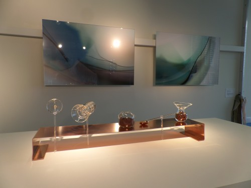 display of lampworked glass vessels in copper fixtures and photographs of glass shards