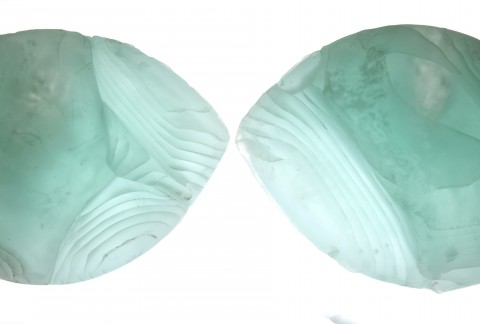 Two green cast glass tear-drop shaped pieces with layered details