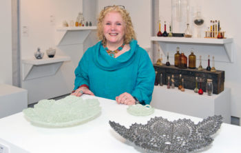 Artist Catherine Carr is standing with her glass works - crocheted dishes . One is a pewter colour and one is like Mother of Pearl.