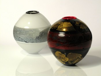 Two glass vessels, with banding around the centre. One is black and white, the other red, black and gold.